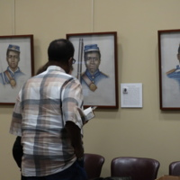 Radcliffe Standing in Front of USCT Portraits